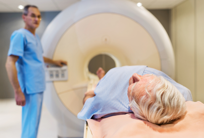 Senior man receiving an MRI Scan. Doctor is in the background. [url=http://www.istockphoto.com/search/lightbox/9786662][img]http://dl.dropbox.com/u/40117171/medicine.jpg[/img][/url]