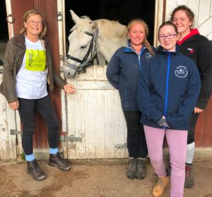 Picture of four women with a horse at a stable door