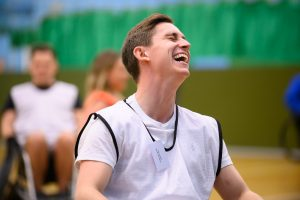 Joshua Hughes playing wheelchair rugby smiling